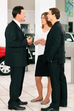 Situation vente chez un concessionnaire, le concessionnaire est parler à un jeune couple, voitures permanent en arrière-plan