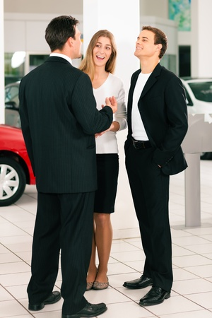 salesperson: Sales situation in a car dealership, the dealer is talking to a young couple, there are cars standing in the background