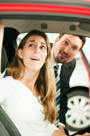 micro drive: Woman buying a car in dealership sitting in her new auto, the salesman talking to her in the background
