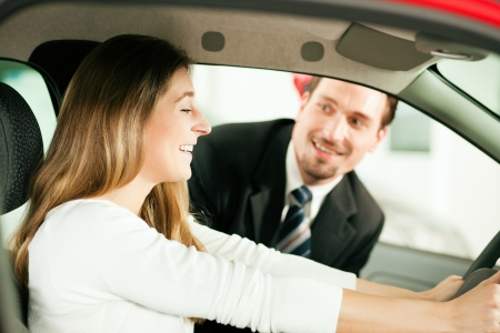 salesperson: Woman buying a car in dealership sitting in her new auto, the salesman talking to her in the background