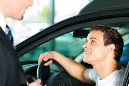 car salesperson: Man buying a car in dealership sitting in his new auto, the salesman talking to him and explaining details   Stock Photo