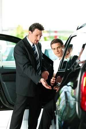 Man buying a car in dealership sitting in his new auto, the salesman talking to him and explaining details   photo
