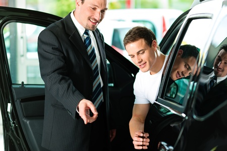 Man buying a car in dealership sitting in his new auto, the salesman talking to him and explaining details Stock Photo - 10260893