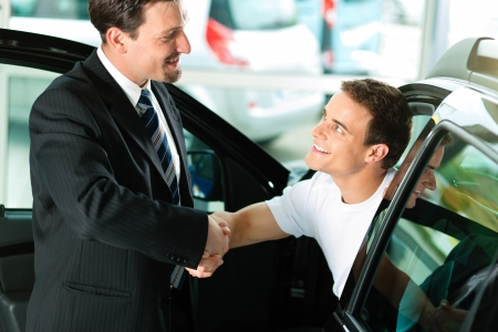micro drive: Man buying a car in dealership sitting in his new auto; they are shaking hands to close the deal