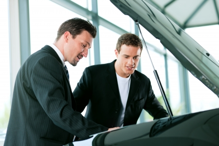 Man buying a car in dealership looking under the hood at the engine Stock Photo - 10260929