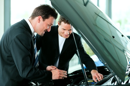 Man buying a car in dealership looking under the hood at the engine Stock Photo - 10260975