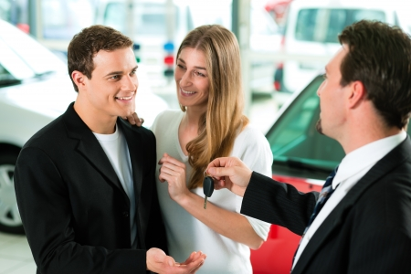 buy car: Sales situation in a car dealership, the dealer is handing auto keys to a young couple, they are excited, cars standing in the background