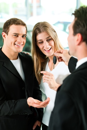 Sales situation in a car dealership, the dealer is handing auto keys to a young couple, they are excited, cars standing in the background Stock Photo - 10260938