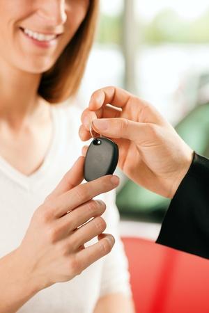 reps: Mujer en un concesionario de coches, comprar un auto, el representante de ventas d�ndole la macro clave, dispar� con foco en manos y clave  Foto de archivo