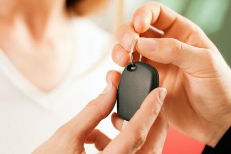 Donna in una concessionaria di auto di acquistare un auto, il rappresentante dandole la chiave, girato macro con messa a fuoco sulle mani e chiave Archivio Fotografico - 10260924