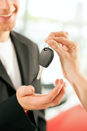 Man at a car dealership buying an auto, the female sales rep giving him the key, macro shot with focus on hands and key  photo
