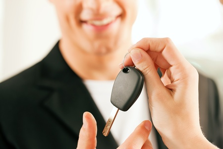 Man at a car dealership buying an auto, the female sales rep giving him the key, macro shot with focus on hands and key Stock Photo - 10260910
