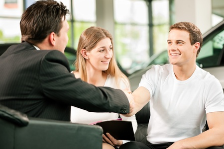 salesperson: Sales situation in a car dealership, the young couple is signing the sales contract to get the new car in the background