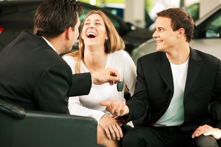Sales situation in a car dealership, the young couple is signing the sales contract to get the new car in the background  photo