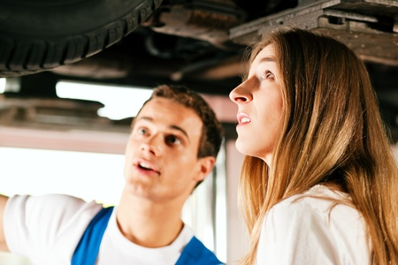 car mechanic: Woman talking to a car mechanic in his repair shop, both are standing underneath the auto which is lifted on a car hoist  Stock Photo