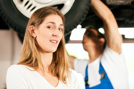 Woman talking to a car mechanic in his repair shop, both are standing underneath the auto which is lifted on a car hoist Stock Photo - 10260956
