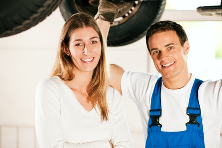 two car garage: Woman talking to a car mechanic in his repair shop, both are standing underneath the auto which is lifted on a car hoist  Stock Photo