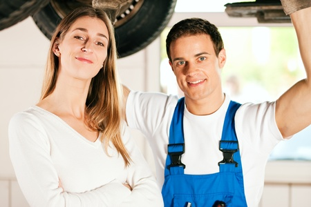 auto shop: Woman standing in front of her car which is lifted on an auto hoist, a mechanic doing a repair underneath the auto  Stock Photo