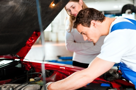 motor mechanic: Woman talking to a car mechanic in his repair shop, both are standing next to the car Stock Photo