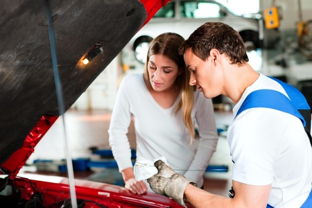 two car garage: Woman talking to a car mechanic in his repair shop, both are standing next to the car Stock Photo