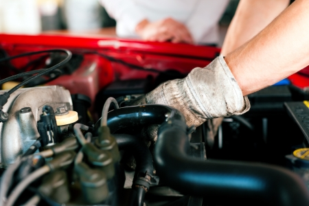 car mechanic in his repair shop standing next to the car - close-up of the engine Stock Photo - 10260980
