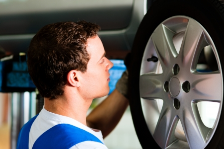 winter tire: Auto mechanic in his workshop changing tires or rims Stock Photo