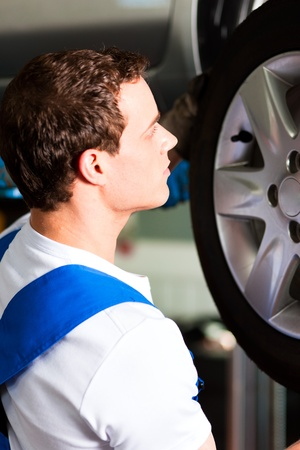 car hoist: Auto mechanic in his workshop changing tires or rims Stock Photo
