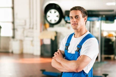 service car: Auto mechanic standing in his workshop in front of a car on a hoist   Stock Photo