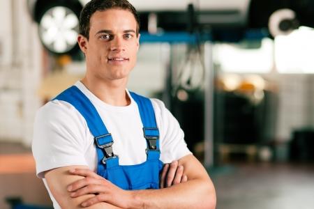 auto monteur: Auto monteur staat in zijn atelier in de voorkant van een auto op een takel