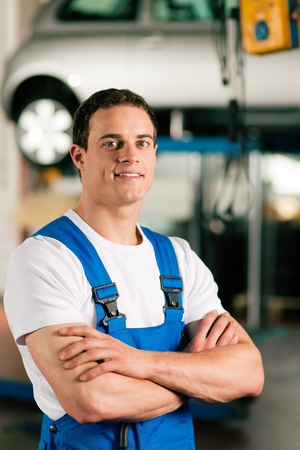 car hoist: Auto mechanic standing in his workshop in front of a car on a hoist   Stock Photo