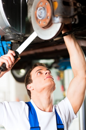 auto garage: Auto mechanic in his workshop looking under a car on a hoist   Stock Photo