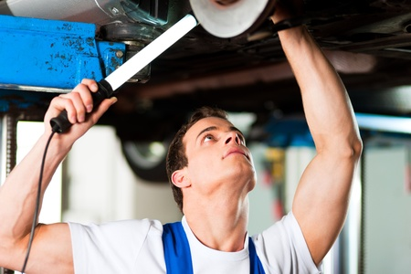 brakes: Auto mechanic in his workshop looking under a car on a hoist   Stock Photo