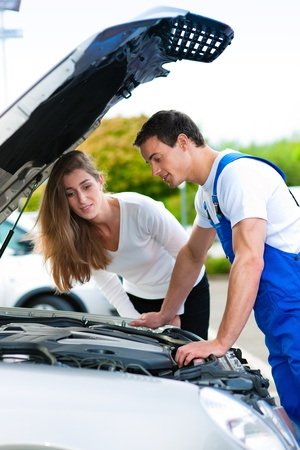 two car garage: Woman talking to a car mechanic in a parking area, both are standing next to the car