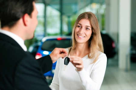 salesperson: Woman at a car dealership buying an auto, the sales rep giving her the key