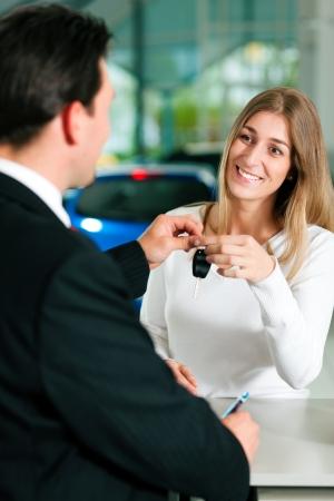 reps: Mujer en un concesionario de coches de comprar un auto, el representante de ventas de darle la clave