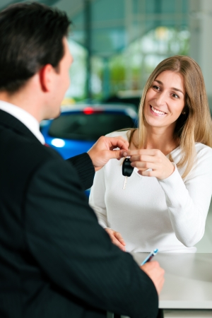 auto dealership: Woman at a car dealership buying an auto, the sales rep giving her the key
