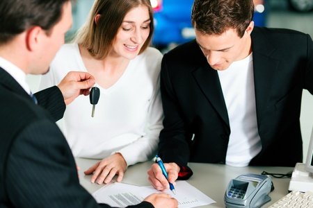 Sales situation in a car dealership, the young couple is signing the sales contract and gets the key for the new car   photo