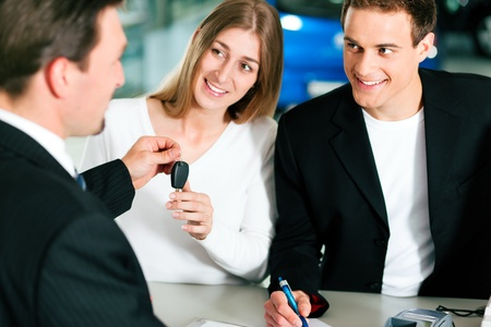 car salesperson: Sales situation in a car dealership, the young couple is signing the sales contract and gets the key for the new car