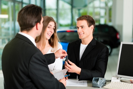 car dealers: Sales situation in a car dealership, the young couple gets the key for the new car   Stock Photo