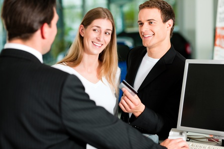 deal: Sales situation in a car dealership, the young couple is giving the credit card to pay for the new car