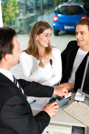 Sales situation in a car dealership, the young couple buys a new car from an agent and pays with credit card  photo