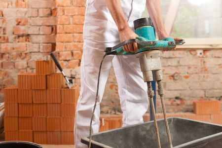 grout: Construction worker mixing concrete or grout with a hand mixer