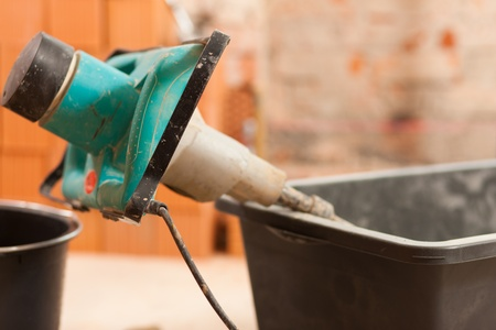 grout: Hand mixer on construction site for mixing concrete or grout