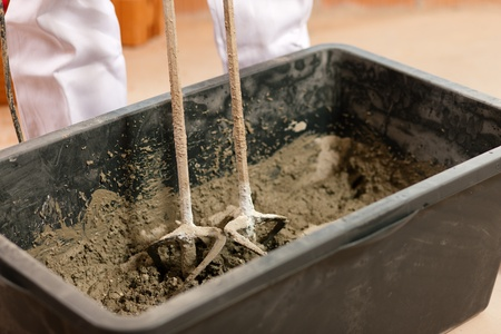 stirring: Construction worker mixing concrete or grout with a hand mixer