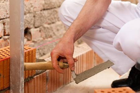 bricklayer: alba�il poniendo ladrillos para hacer una pared, est� comprobando su trabajo
