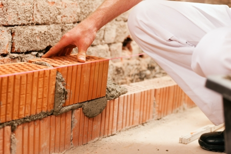bricklayer: bricklayer laying bricks to make a wall, he is putting grout on top of a brick