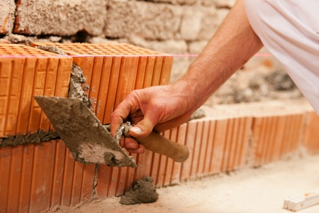 brick mason: bricklayer laying bricks to make a wall, he is putting grout on top of a brick