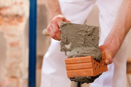 bricklayer: alba�il poniendo ladrillos para hacer una pared, est� poniendo la boquilla de un ladrillo  Foto de archivo