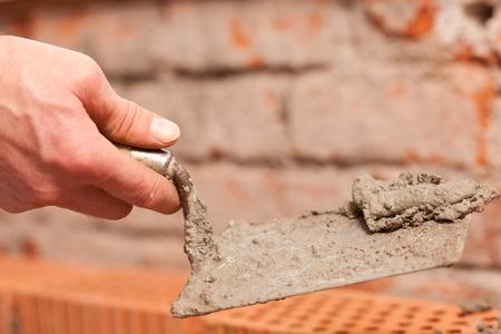 bricklayer: alba�il colocando ladrillos para hacer una pared, �l est� poniendo cemento en la parte superior de ladrillos