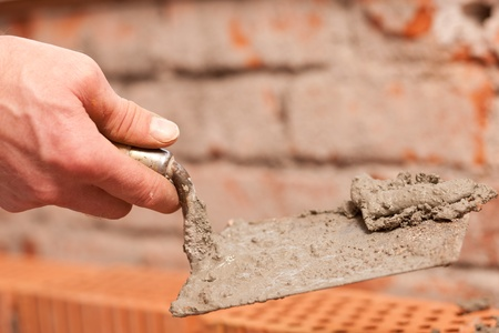 grout: bricklayer laying bricks to make a wall, he is putting grout on top of bricks